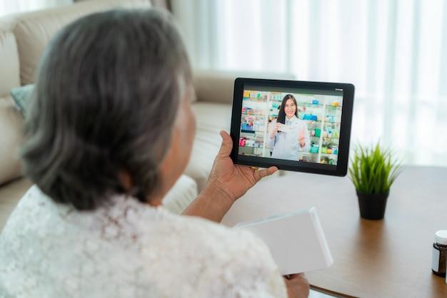 ビデオ会議を使用してアジアの年配の女性は、ビデオコールを介して病気や薬について薬局のコンサルティングをオンラインで相談します。遠隔医療、遠隔医療、オンライン病院。