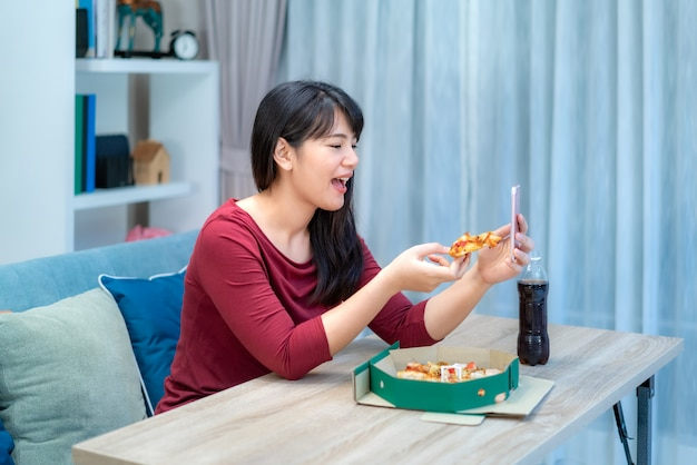 アジアの女性仮想ハッピーアワーディナーとデジタルタブレットとのビデオ会議で彼女のボーイフレンドと一緒にオンラインでピザ料理を食べる