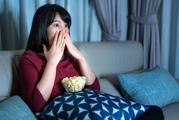 Молодая азиатская женщина смотря кино или новости неизвестности телевидения смотря сотрясенный и возбужденный есть попкорн поздно вечером дома живя кресло.