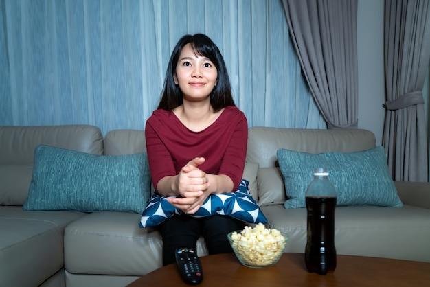 Молодая азиатская женщина смотря кино или новости неизвестности телевидения смотря счастливый и ослабляя и есть кресло живущей комнаты попкорна поздно ночью дома.
