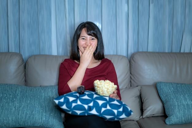 Молодая азиатская женщина смотря кино или новости неизвестности телевидения смотря счастливый и смешной и есть кресло живущей комнаты попкорна поздно ночью дома во время домашней изоляции.