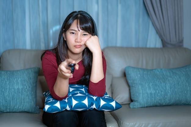 テレビのサスペンス映画やニュースを見て若いアジア人の女性は、家の隔離時に自宅のリビングルームのソファで深夜または退屈そうに見えます。