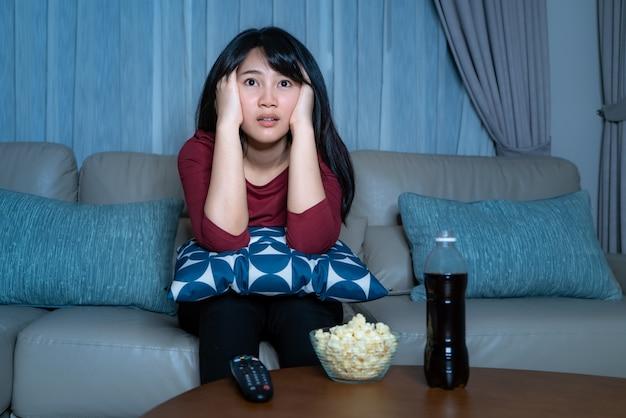 Молодая азиатская женщина смотря кино или новости неизвестности телевидения смотря сотрясенный и возбужденный есть попкорн поздним вечером дома живя кресло во время времени домашней изоляции.