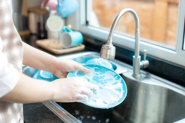 魅力的な若いアジア女性の手を閉じるは、毎日のハウスキーピングルーチンについて自由時間を使用して在宅中に自宅で掃除をしながら台所の流しで皿を洗っています。