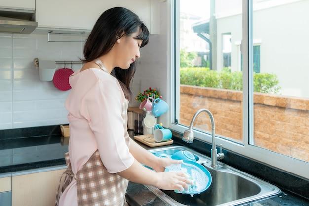 魅力的な若いアジア女性は、毎日のハウスキーピングルーチンについて自由時間を使用して在宅中に自宅で掃除をしながら台所の流しで皿を洗っています。