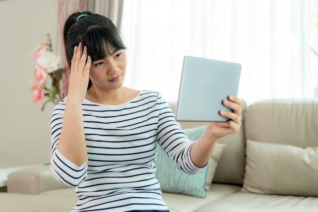 Азиатская женщина звоня видео- с ее доктором с ее головной болью чувства на консультации обслуживания цифровой технологии здравоохранения цифровой таблетки онлайн пока остающся дома.