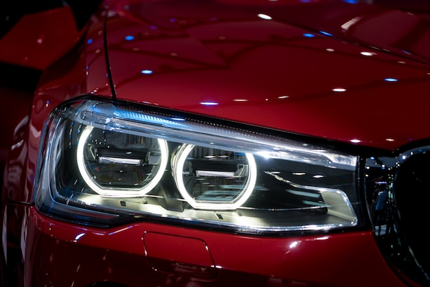Макрофотография фары современного красного автомобиля во время включения света в ночное время.