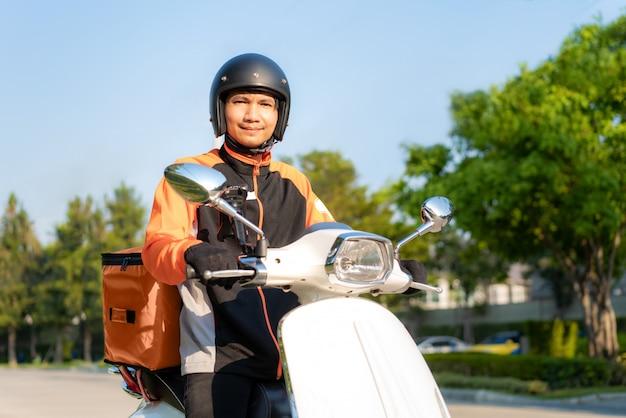 Азиатский курьер человека на самокате поставляя еду на улицах городка с горячей доставкой еды от взятия прочь и ресторанов к дому, срочной доставки еды и ходя по магазинам онлайн концепции.