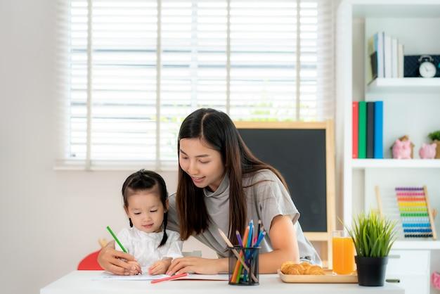 家庭、ホームスクーリング、遠隔学習で色鉛筆で本に絵を描いている母を持つアジアの幼稚園学生の女の子。