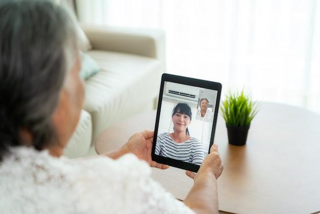Азиатская пожилая женщина разговаривает онлайн вместе со своей дочерью