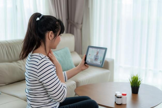 Вид сзади женщина делает видео звонок со своим врачом с ее чувство боли в горле