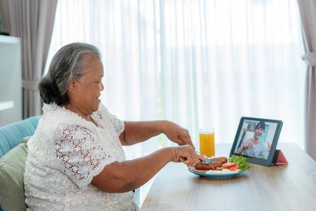 アジアの高齢女性仮想ハッピーアワー会議と彼女の娘と一緒にオンラインで食べ物を食べる