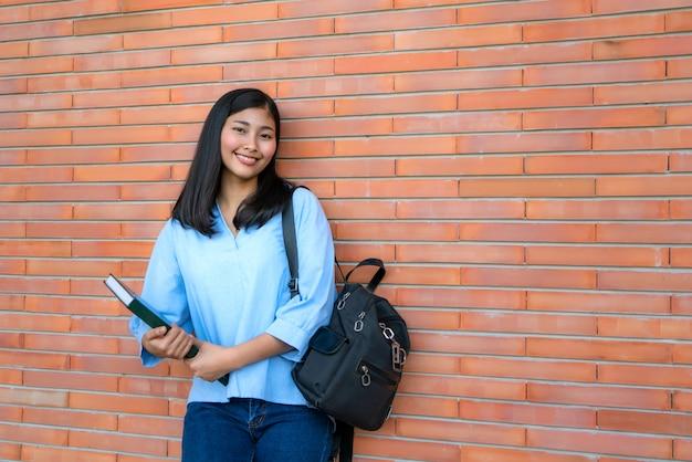 Азиатский усмехаясь студент женщины держа книгу