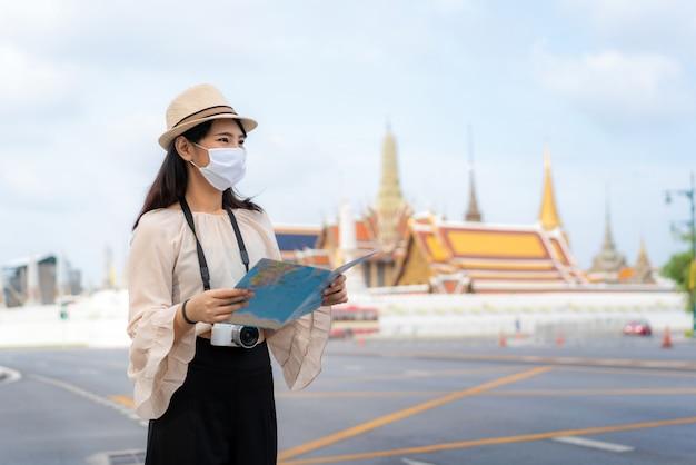 Туристы азиатской женщины счастливые для того чтобы путешествовать нося маска