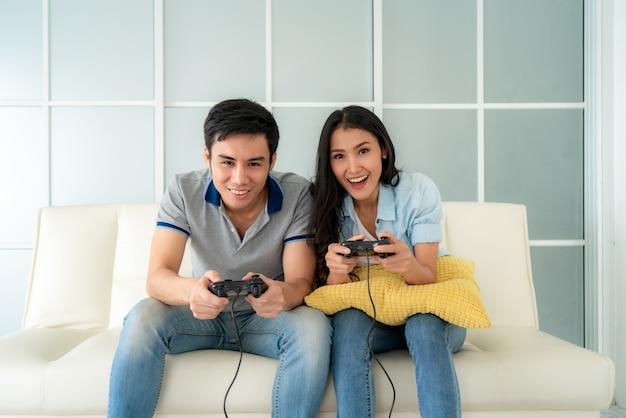 Азиатская пара мужчина и женщина играть в видео игры дома