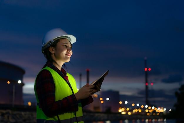 Инженер нефтехимии азиатской женщины работая на ноче с цифровой таблеткой внутри завода рафинадного завода нефти и газ