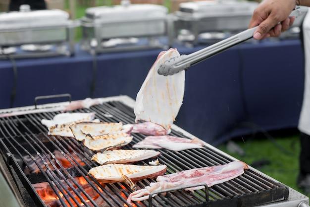 シェフはイカをアジアのスパイスで焼き上げて調理しています