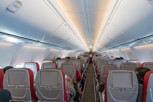 Интерьер самолета с пассажирами на сиденьях и стюардессой в форме ходьбы по проходу.