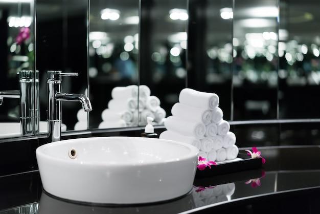 ホテル内の洗面器の蛇口と白いタオル付きのバスルームのインテリア。最近のバスルームのデザイン。