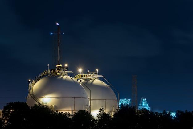 Ландшафт индустрии нефтеперерабатывающего предприятия с баком для хранения масла в ноче.