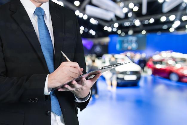 Продавец руки, держа торговое бронирование нового автомобиля отображается в выставочном зале