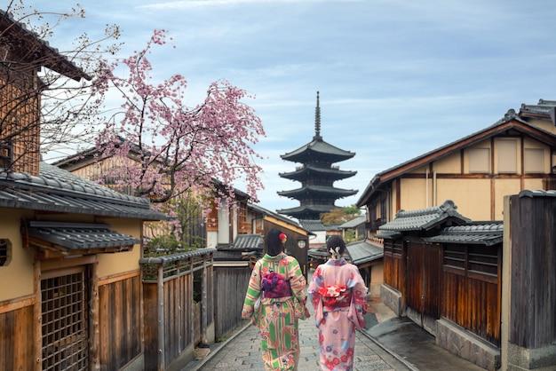 日本の京都の八坂パゴダと三年坂通りで伝統的な日本の着物を着ている女性