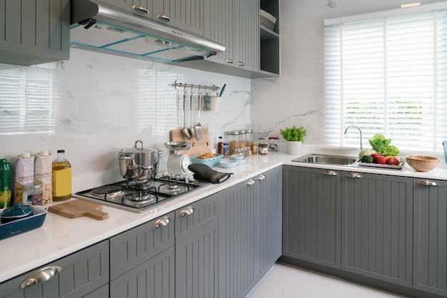 キッチン用木製品、シェフアクセサリー。白いタイルの壁が付いている吊り銅キッチン。