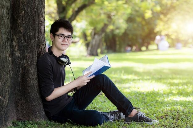 アジアの若いハンサムな男子学生が自然の中で本を読んでいます。一人の学生。