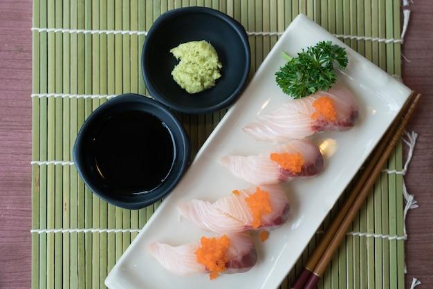 日本のソースと緑の葉の装飾と一緒に白いプレートにハマチ寿司