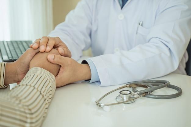 フレンドリーな男医師両手励ましのために机に座って患者の手を握って