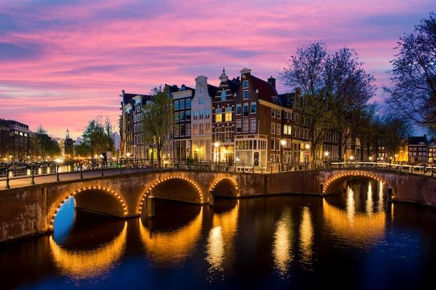 運河とオランダのアムステルダムの夜の典型的なオランダの家