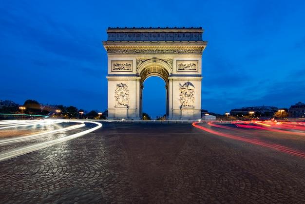 フランス、パリの凱旋門と夜のパリ通り。