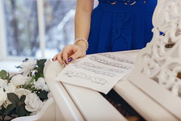 音符は女性の手の近くの白いピアノのクローズアップにあります。