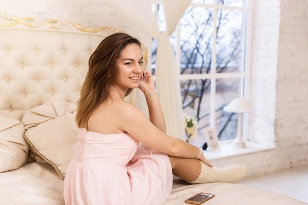 ヘッドフォンとピンクのドレスの若い女性のクローズアップ