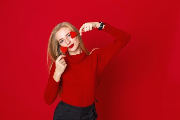 赤い背景の上のセーターで楽しい笑顔の女性