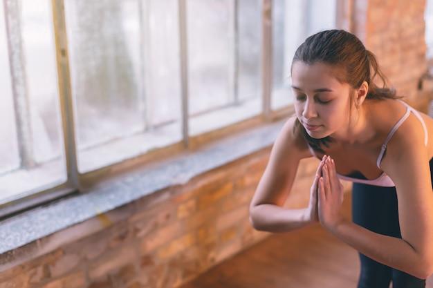 窓の近くのヨガの部屋で一人でヨガをやっている若い女の子