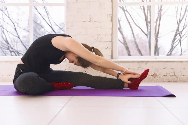 ヨガの練習をしている女性は、室内のヨガマットの明るい部屋の床の片足に頭を曲げます。