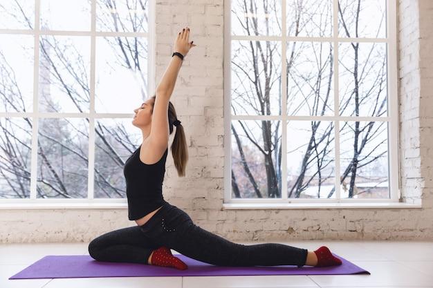 片足ハトの運動をしている、窓の近くのヨガの練習若いスポーティな女性