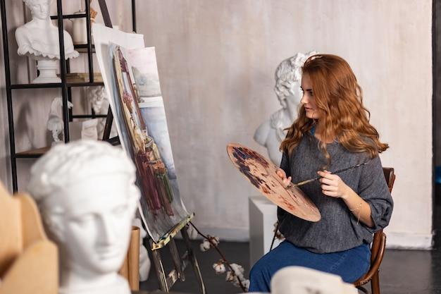 前景に手でパレットを持つ幸せなアーティストの肖像画
