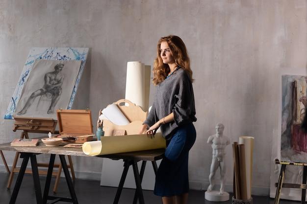 彼女のスタジオでアートプロジェクトに取り組んでいるゴージャスな女性アーティストの肖像画
