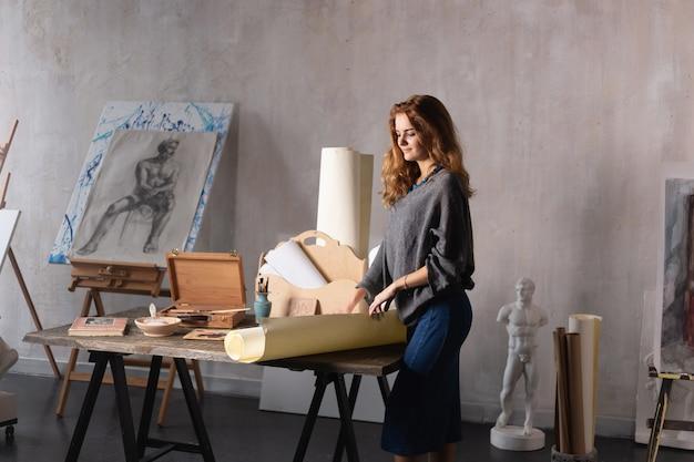 ブラシとパレットを持つ女性画家が彼女の手に、空のキャンバスの前に立って、描画します。