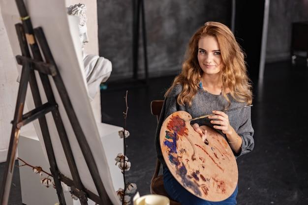 フォアグラウンドで手にパレットを持つ幸せな芸術家の肖像