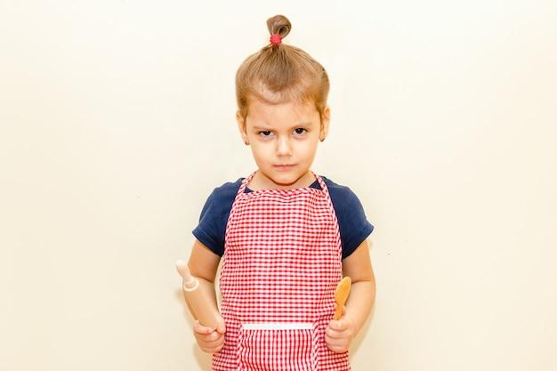 Хмурившаяся маленькая девочка с фартуком от шеф-повара держит деревянную скалку и ложку на бежевом фоне