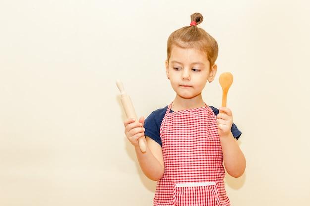 Глядя с интересом, маленькая девочка с фартуком шеф-повара держит деревянную скалку и ложку на бежевом фоне