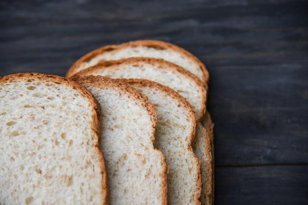 スライスされたパンのクローズアップトップビュー - 全粒小麦パンの木製の暗闇の中でカット