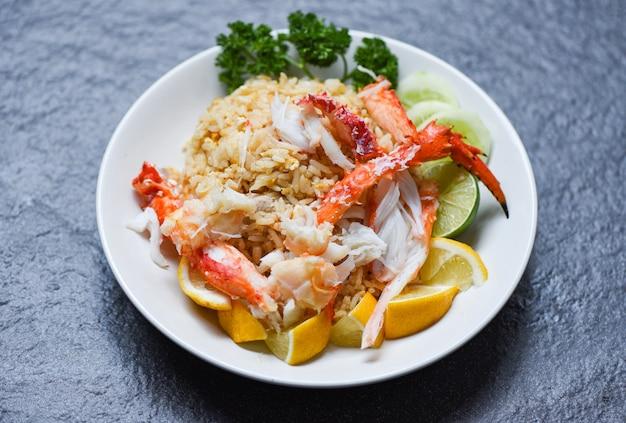 Жареный рис из крабовых морепродуктов - здоровая пища жареный рис с крабовыми ножками с яйцом лимоном и огурцом на белой тарелке