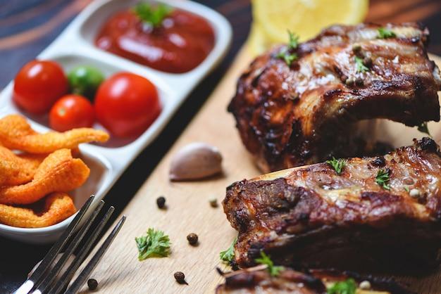 Жареные свиные ребрышки на гриле с томатным кетчупом и пряными травами на столе