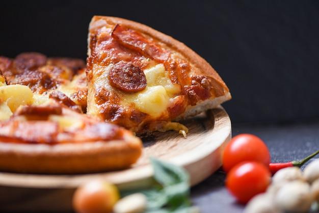 木製のトレイと暗闇の中でトマト唐辛子バジルの葉のピザのスライス