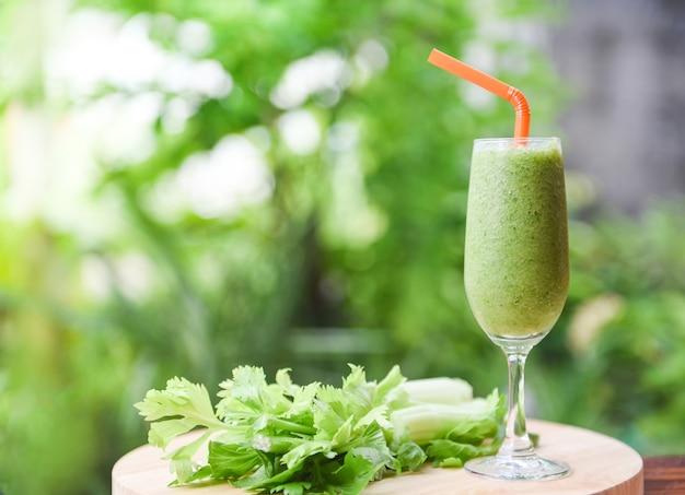 自然の緑の木の板に野菜ジューススムージー夏と新鮮なセロリの茎