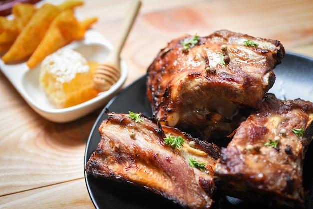 Жареные свиные ребрышки на гриле с медово-сладким соусом и пряными травами на столе